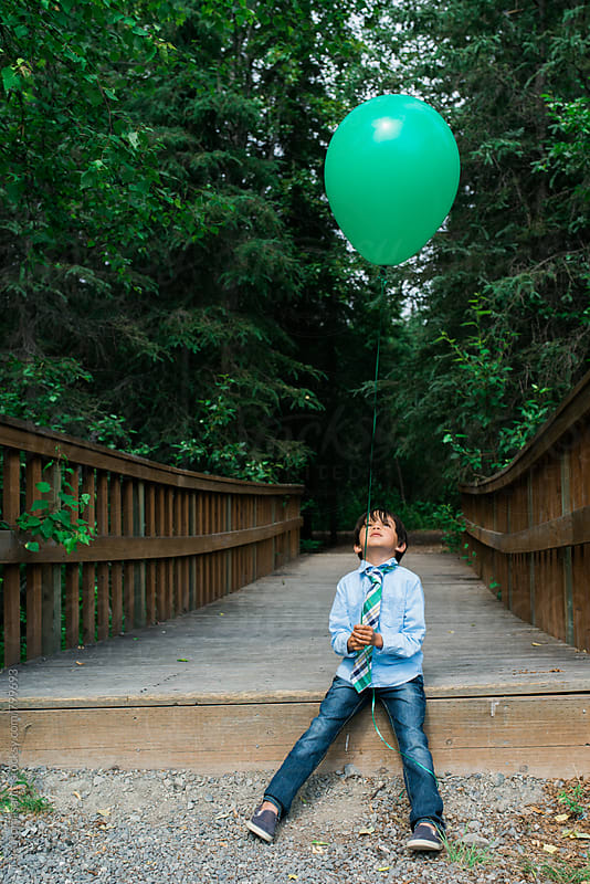 young boy in a tie looks up a balloon by Tara Romasanta for Stocksy United