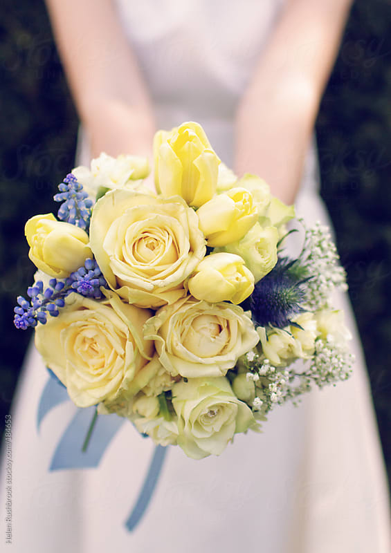 Bridesmaid holding a bouquet of spring flowers by Helen Rushbrook for Stocksy United