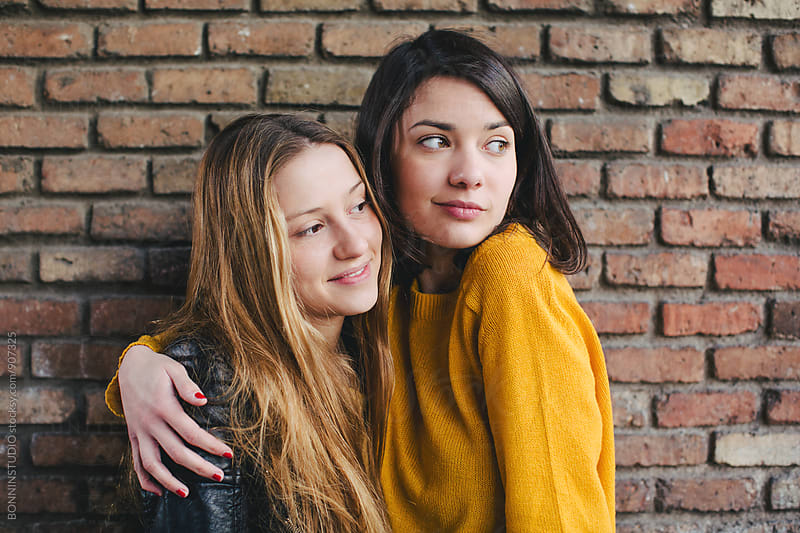 Best friends together in front of a brick wall. by BONNINSTUDIO for Stocksy United