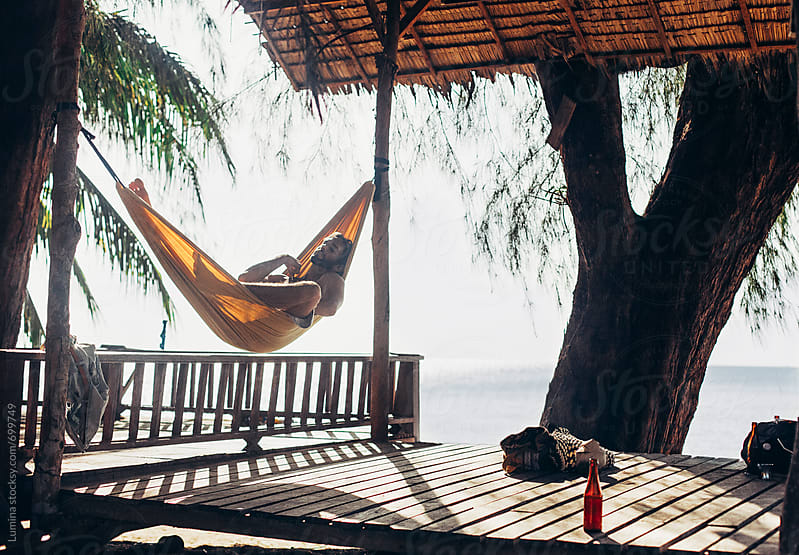 Man Sleeping in a Hammock at the Beach by Lumina for Stocksy United