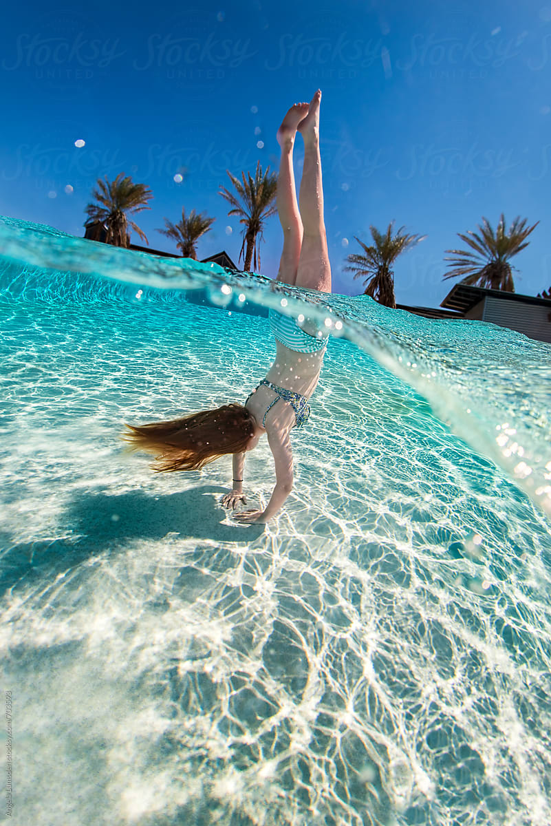 Girl in a bikini doing a handstand in a swimming pool ...