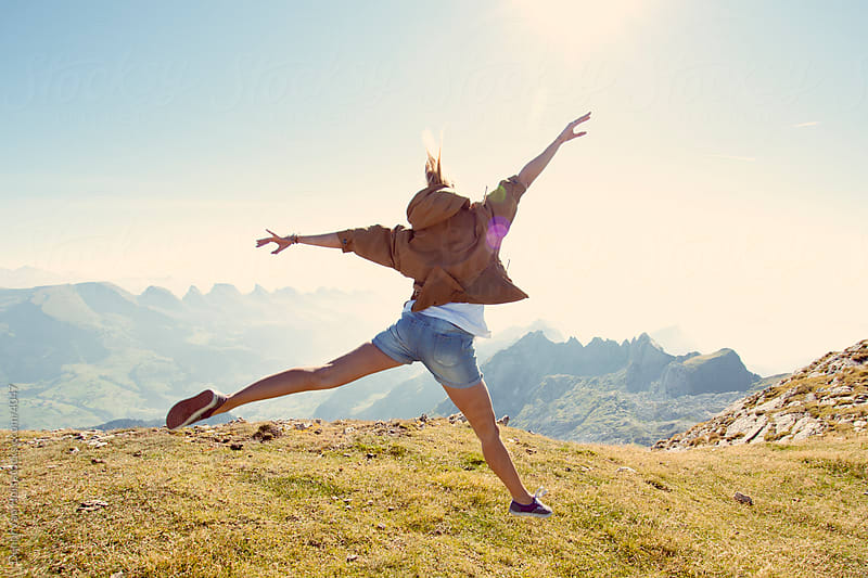Happy young woman jumps in the air on the of a mountains and enjoying the view by Denni Van Huis for Stocksy United