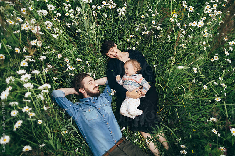 Young couple and their baby girl laying in camomile field by Evgenij Yulkin for Stocksy United