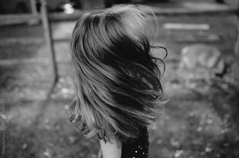 Girl swinging hair outdoors in black and white. by Kelsey Gerhard for Stocksy United