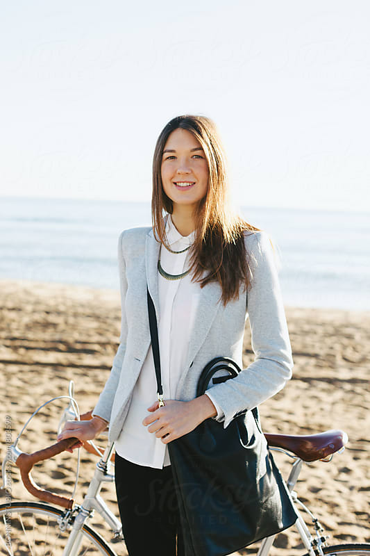 Portrait of a businesswoman standing with her vintage bicycle in front of the beach. by BONNINSTUDIO for Stocksy United