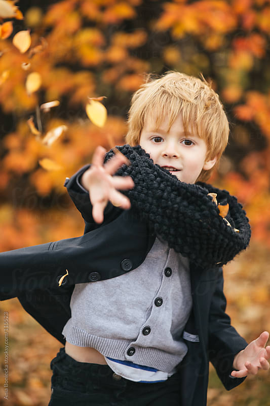 A young boy throwing yellow leaves at the camera smiling by Ania Boniecka for Stocksy United