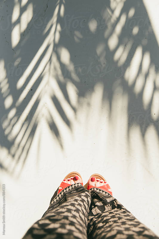 Toes in sandals, photographed from where I stand with palm leaf shadows on the ground by Maresa Smith for Stocksy United
