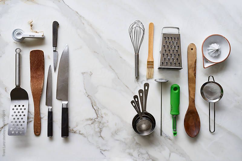 Different kitchenware tools on marble table by Trent Lanz for Stocksy United