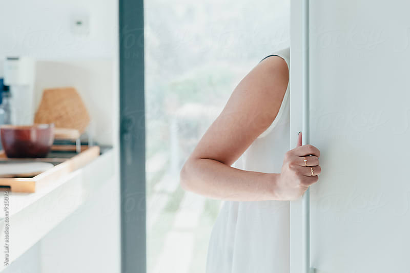 Woman looking into a fridge by Vera Lair for Stocksy United