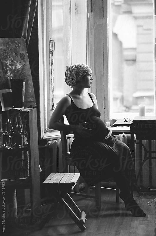 A black and white film portrait of a young beautiful  pregnant woman by Anna Malgina for Stocksy United