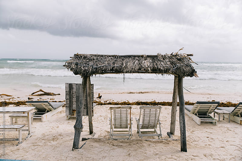 Palm Thatched roof over beach chairs by Christian Gideon for Stocksy United