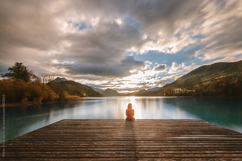 young man in red jacket sitting on a jetty  at a lake enjoying the sunrise by Leander Nardin for Stocksy United