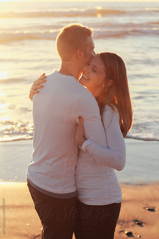 Young couple in love hugging on the beach at sunset by paff for Stocksy United