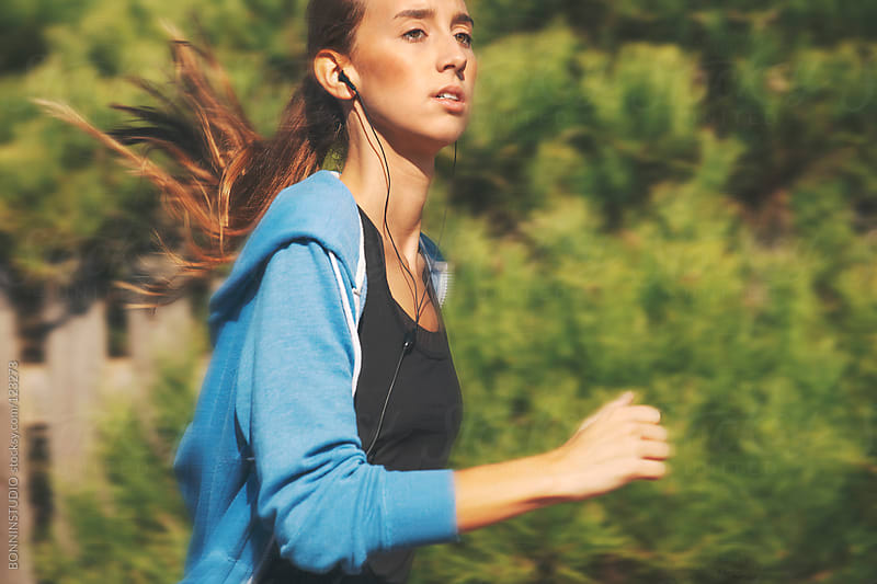 Young woman running in the park. Listening music with headphones. by BONNINSTUDIO for Stocksy United