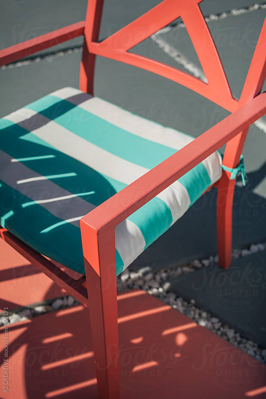 Peach colored chair by the pool. by Robert Zaleski for Stocksy United