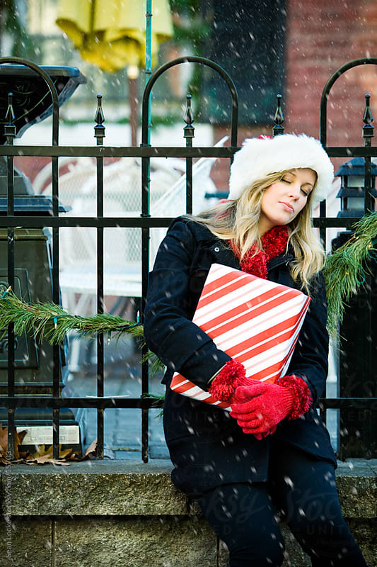 Christmas: Tired Christmas Shopper Rests in Snow by Sean Locke for Stocksy United