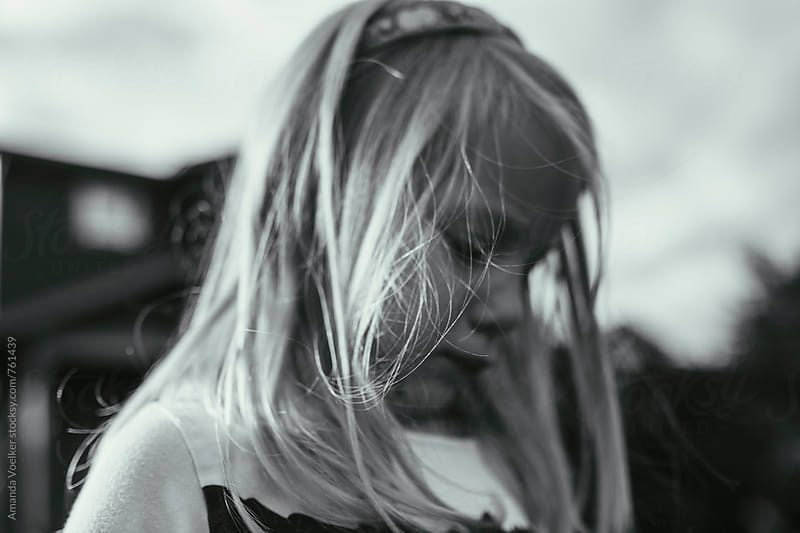 Profile of a young Girl in Black and White with Hair Whisping in the Wind by Amanda Voelker for Stocksy United