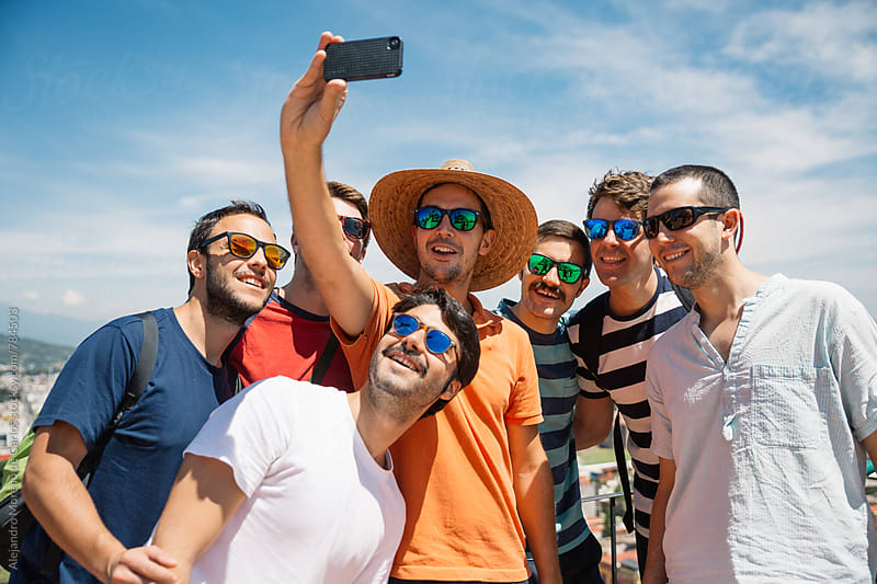 Young group of men taking a selfie with their phone on a blue sky sunny day by Alejandro Moreno de Carlos for Stocksy United