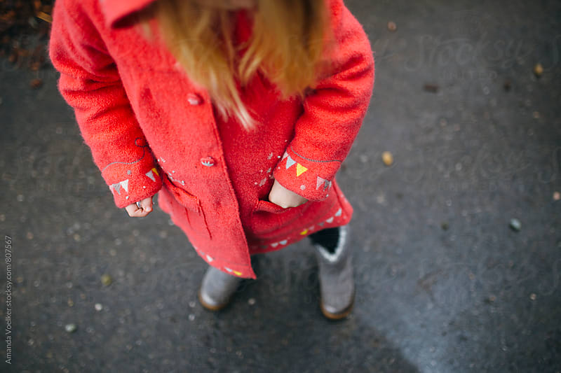 A Little Girl Puts Something in her Coat Pocket by Amanda Voelker for Stocksy United