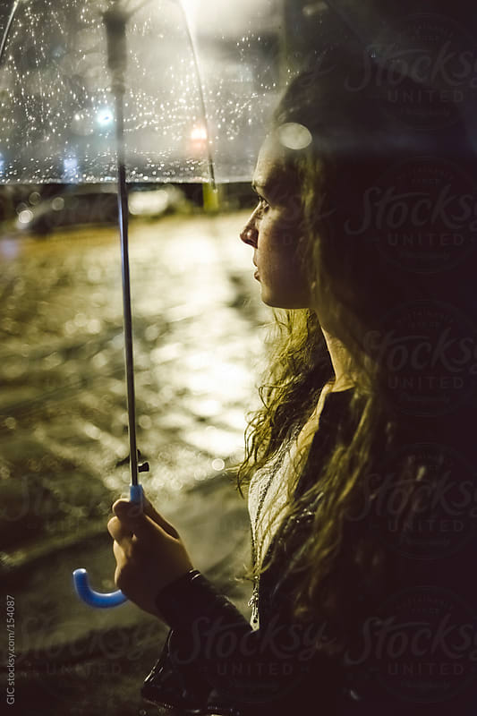 Young woman holding ombrella in the rain by GIC for Stocksy United