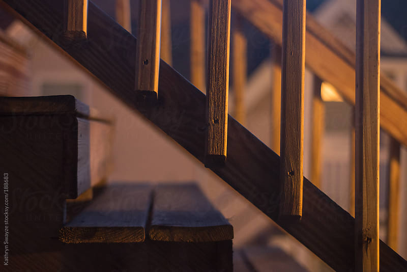 Wooden steps and railing at twilight by Kathryn Swayze for Stocksy United