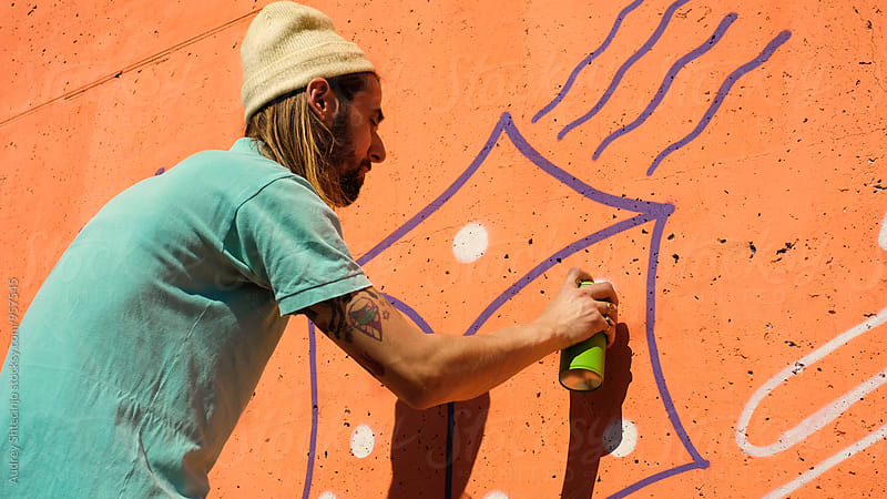 Young hip male spraying graffiti on wall during sunny day by Marko Milanovic for Stocksy United