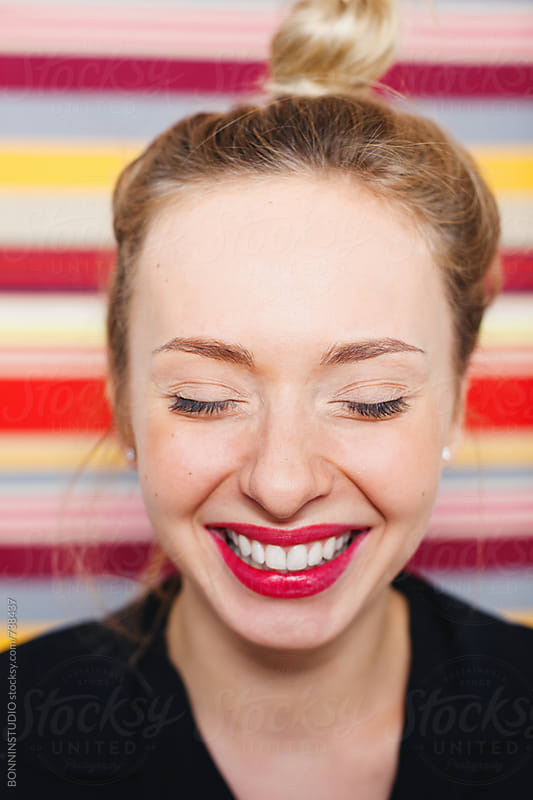 Woman with red lips laughing in front of a striped wall. by BONNINSTUDIO for Stocksy United