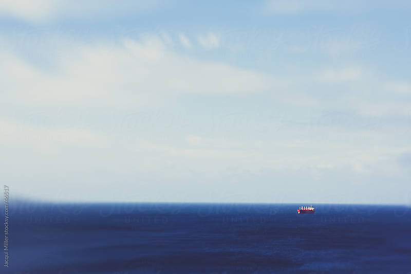 Solitary red ship on an expanse of blue ocean by Jacqui Miller for Stocksy United