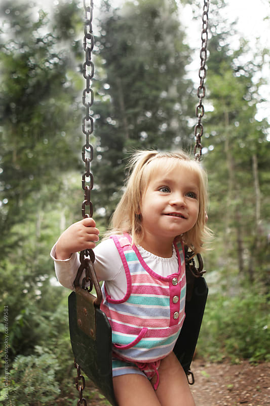 Blonde toddler girl smiling on swing in the park by Dina Giangregorio for Stocksy United