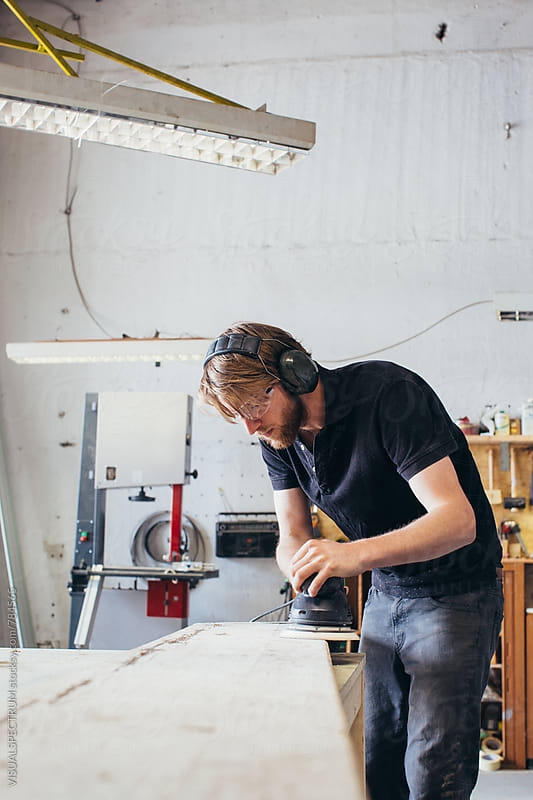 Young Blond Carpenter Sanding Wood Plank With Random Orbital Sander in Bright Workshop by Julien L. Balmer for Stocksy United
