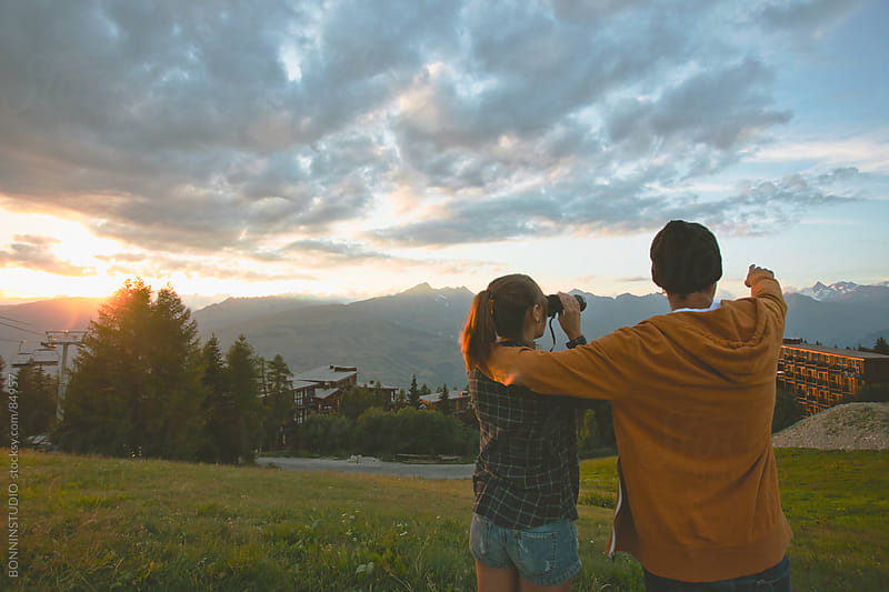 Back view of cute cuple with binoculars on a beautiful sunset in les Alps, France. by BONNINSTUDIO for Stocksy United