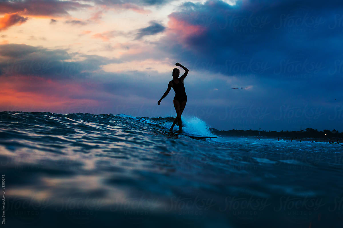 Silhouette Of Woman In The Ocean Surfing Wave At Sunset