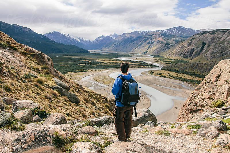 Young man facing backwards on Patagonia landscape on adventure travel by Alejandro Moreno de Carlos for Stocksy United