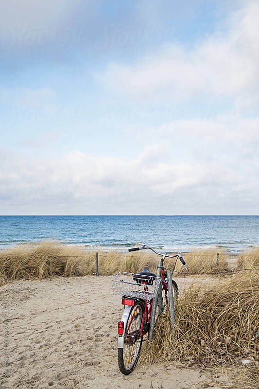 Bicycle parked in dunes near the sea by Melanie Kintz for Stocksy United