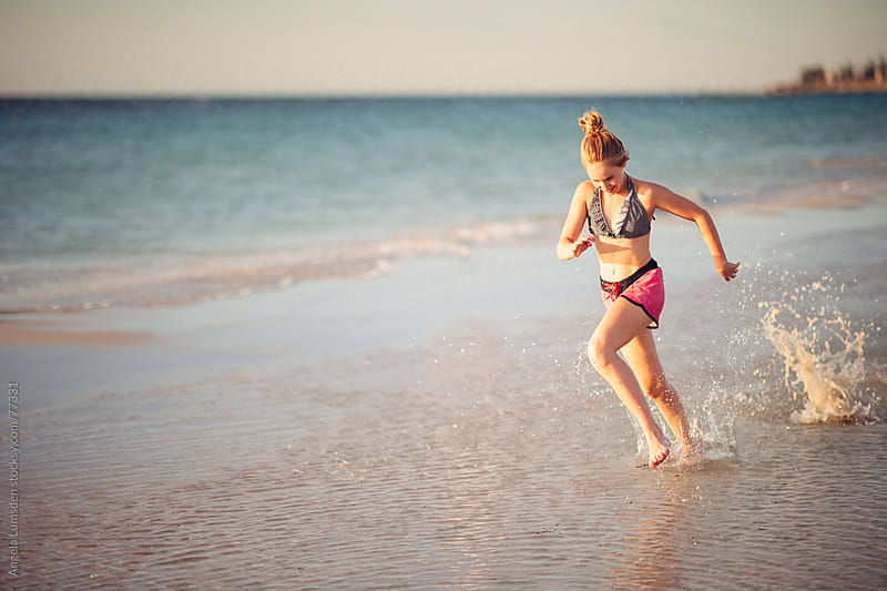 Girl running through water at the beach by Angela Lumsden for Stocksy United
