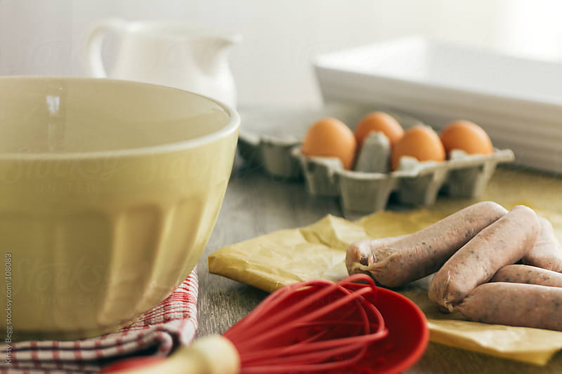 Cooking scene with eggs and sausages, horizontal by Kirsty Begg for Stocksy United