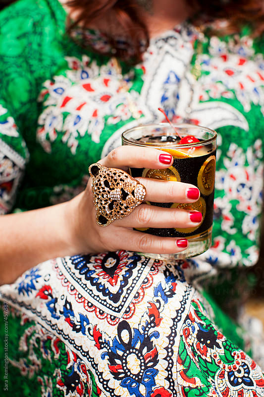 Woman Holding Drink at Seventies Party by Sara Remington for Stocksy United