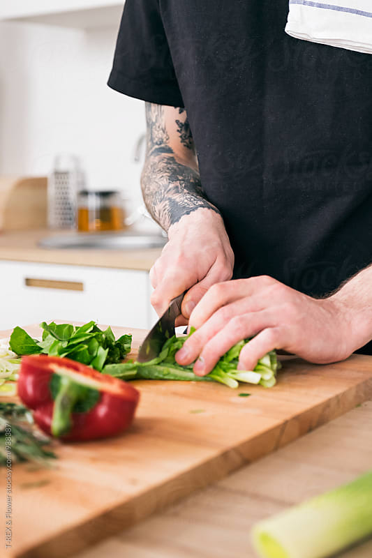 Man cooking at home with knife by Danil Nevsky for Stocksy United