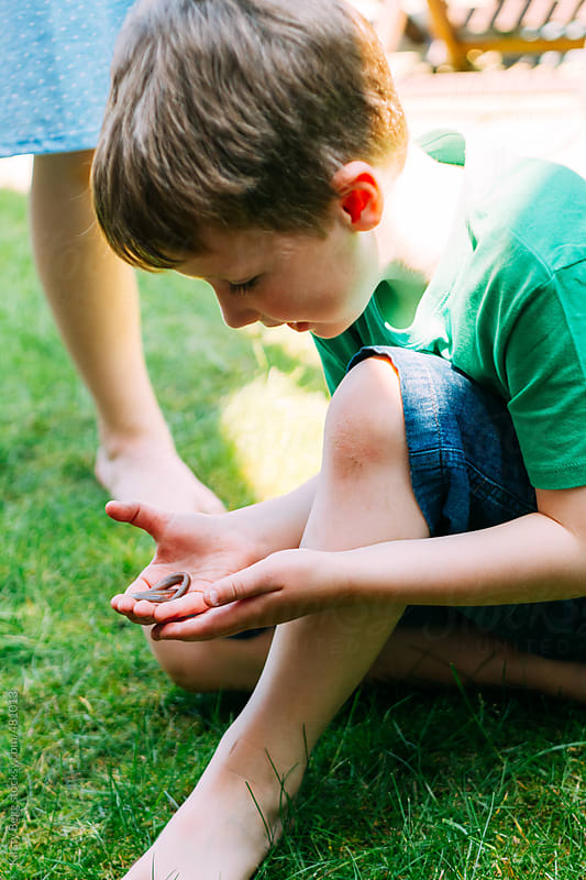 Little boy holds worm in hand by Kirsty Begg for Stocksy United
