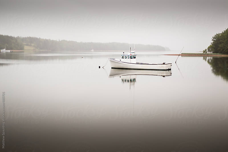 Fishing work boat floating on calm glassy water at dawn by Matthew Spaulding for Stocksy United