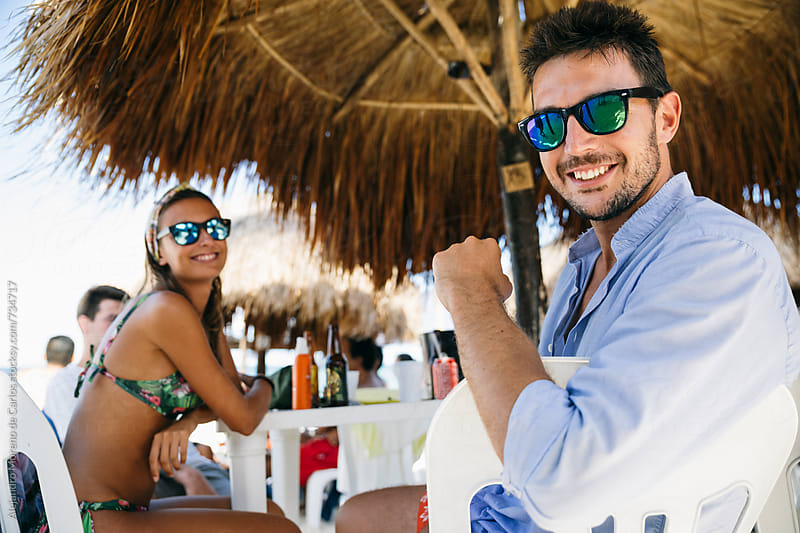 Happy young man and woman in a beach restaurant enjoying a meal with their friends by Alejandro Moreno de Carlos for Stocksy United