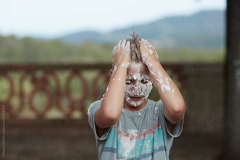 Child playing and covering his hair with whipped cream by Miquel Llonch for Stocksy United
