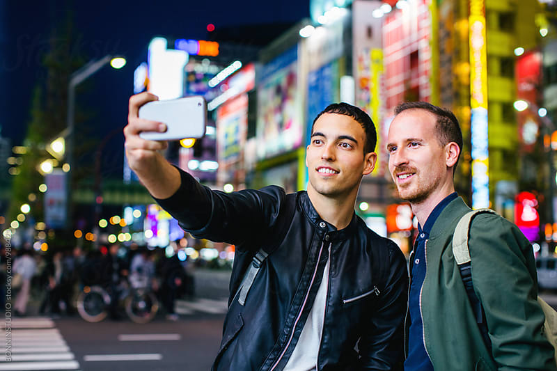 Tourist friends taking a selfie of Tokyo skyscraper at night. by BONNINSTUDIO for Stocksy United