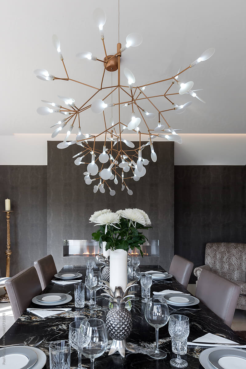 Black granite dining table set for dinner with large ceiling ...