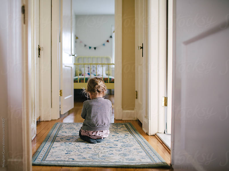 little girl playing in a hallway by Meaghan Curry for Stocksy United
