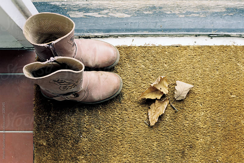 Winter boots and autumn leaves on a doormat by Helen Rushbrook for Stocksy United
