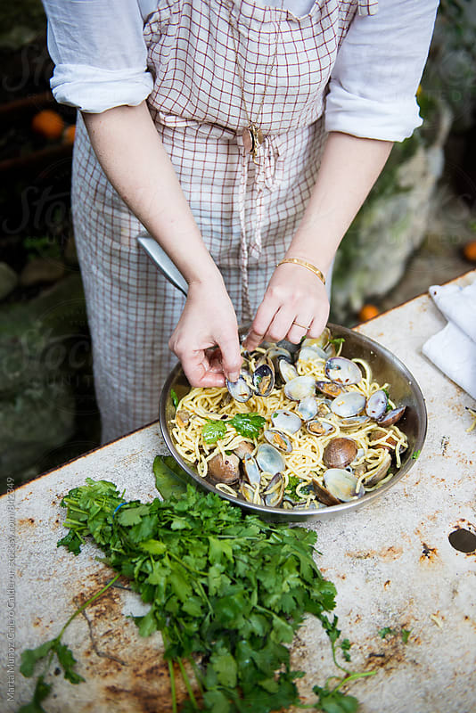 Woman holding a pan with spaghetti vongole by Marta Muñoz-Calero Calderon for Stocksy United