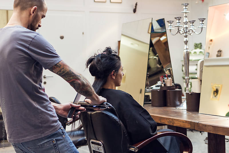 woman is getting her hair straightened with a flat iron by Leander Nardin for Stocksy United