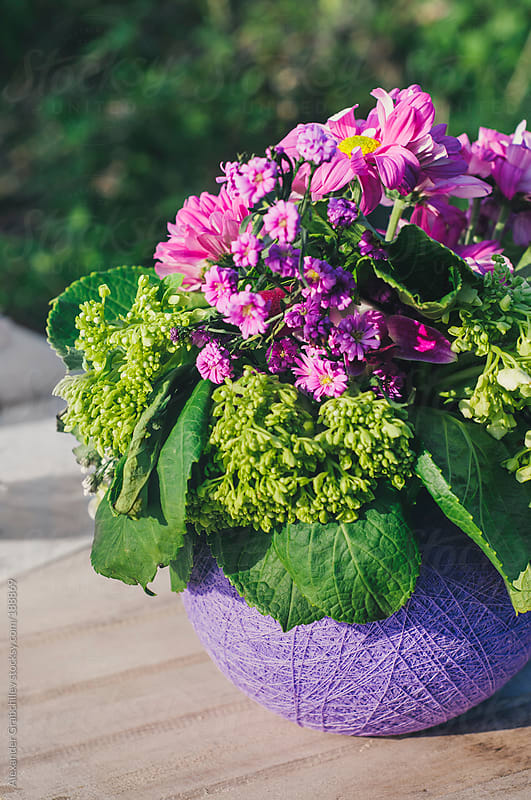 Purple Bunch Of Flowers On Vintage Table Outdoors by Alexander Grabchilev for Stocksy United