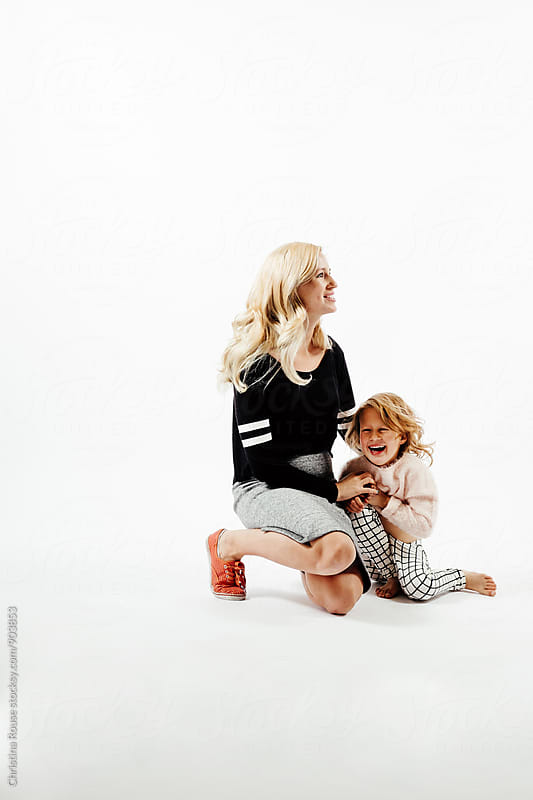 Mother tickles laughing child by Christina Rouse for Stocksy United